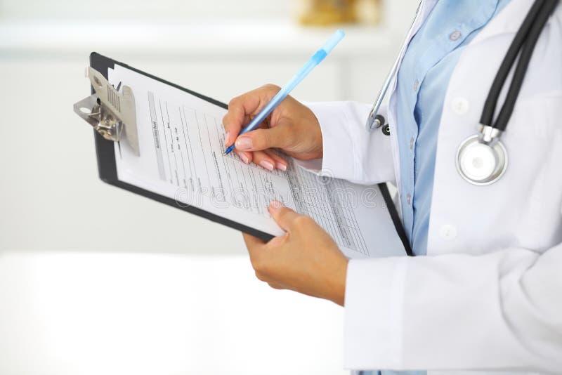 Primo piano di un medico femminile che riempie forma medica alla lavagna per appunti mentre stando diritto nell'ospedale immagini stock