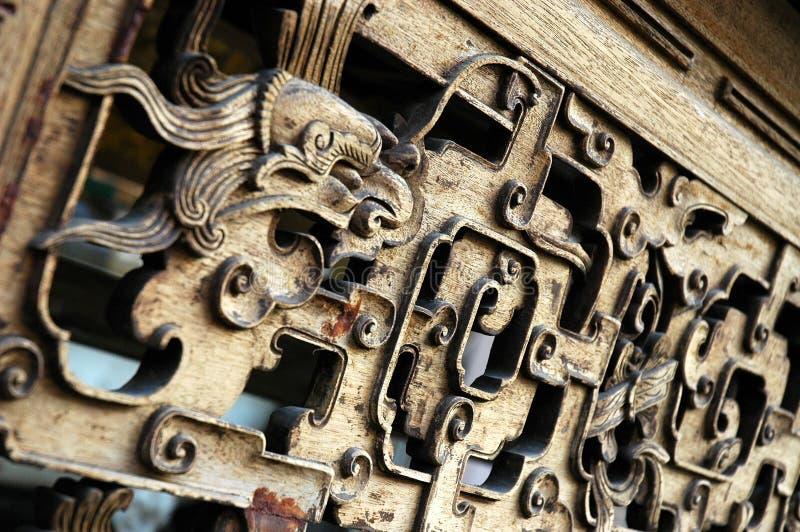 Primo piano di un motivo di una testa del drago su una mobilia di legno fotografia stock