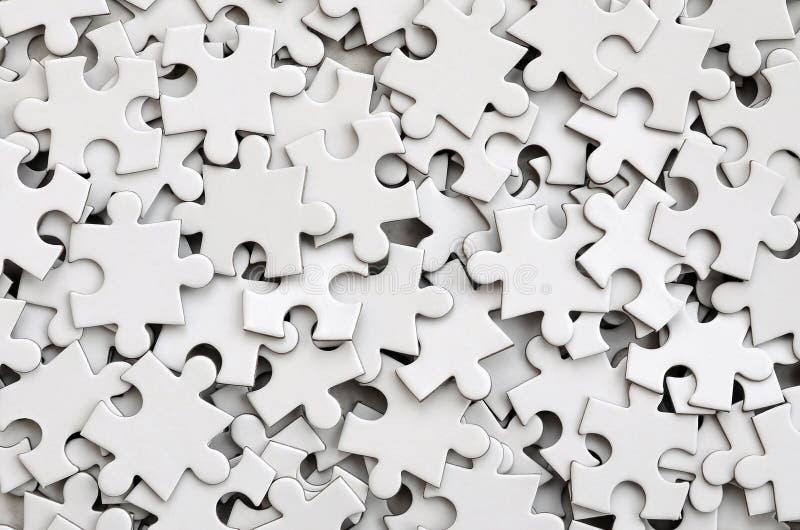Primo piano di un mucchio degli elementi incompiuti di un puzzle bianco Un gran numero dei pezzi rettangolari da un grande mosaic immagine stock libera da diritti