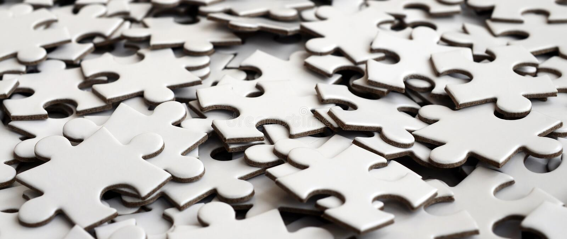 Primo piano di un mucchio degli elementi incompiuti di un puzzle bianco Un gran numero dei pezzi rettangolari da un grande mosaic immagine stock