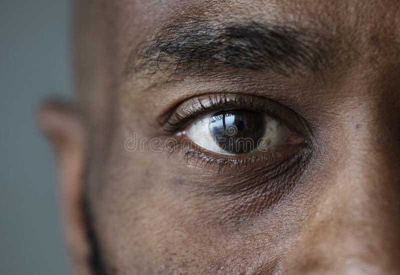 Primo piano di un occhio di un'espressione facciale dell'uomo di colore immagine stock libera da diritti