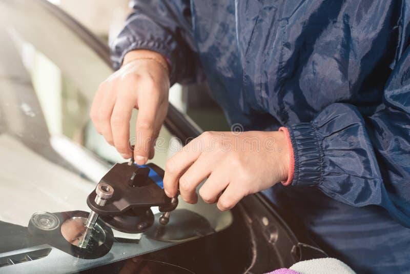 Primo piano di un riparatore professionista del parabrezza che lavora con il riempitore idraulico della crepa del polimero Elimin fotografia stock libera da diritti