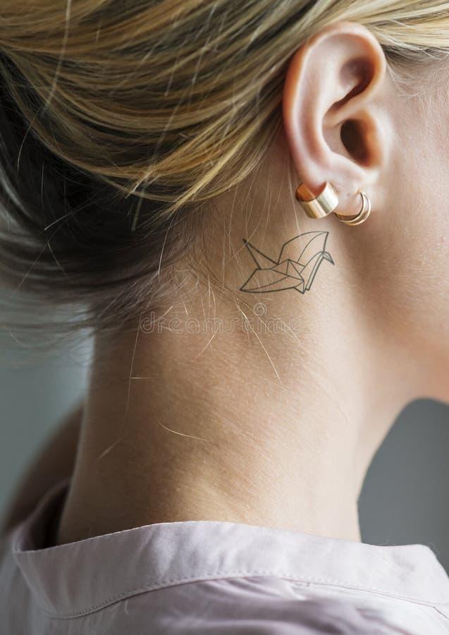 Primo piano di un semplice dietro il tatuaggio dell'orecchio di una giovane donna fotografie stock