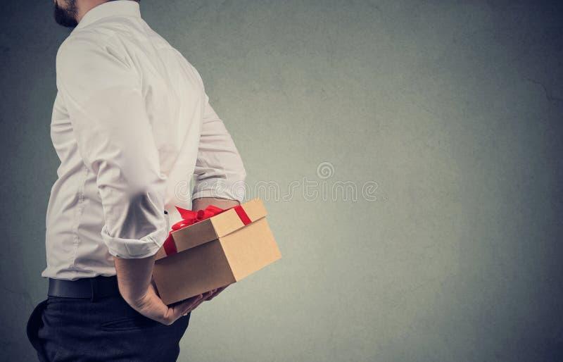 Primo piano di un uomo in camicia bianca che tiene un contenitore di regalo dietro il suo indietro immagine stock