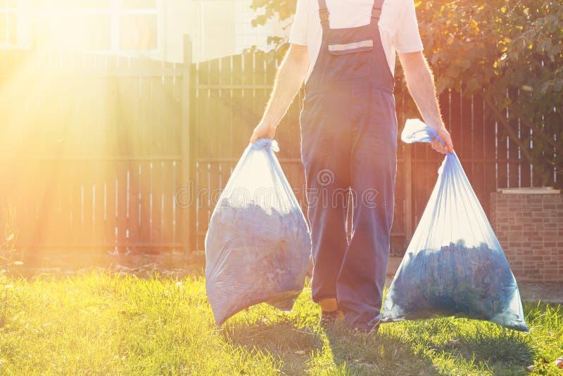 Primo piano di un uomo di camminata in un'uniforme blu, nelle mani delle borse di immondizia Luce solare a sinistra immagine stock