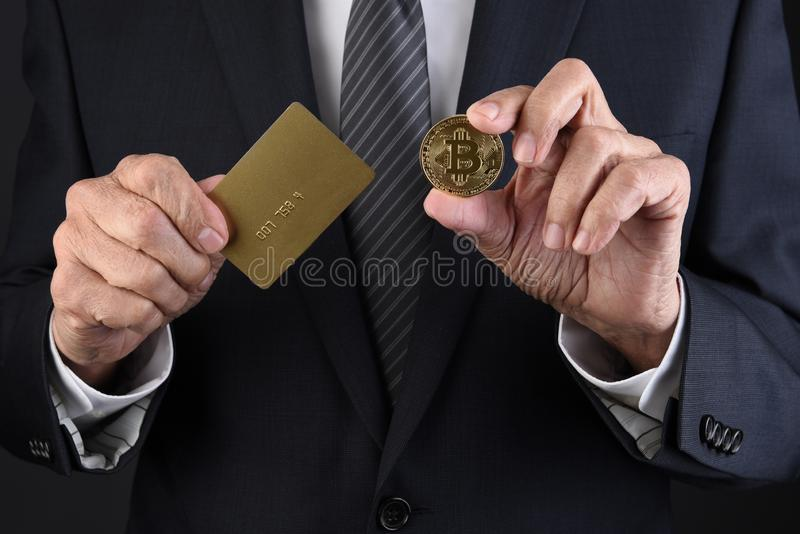 Primo piano di un uomo d'affari che tiene una carta di credito in un habd e un BitCoin in sua altra mano fotografia stock