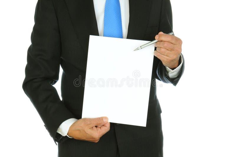 Uomo d'affari facendo uso della penna da indicare a carta fotografia stock libera da diritti