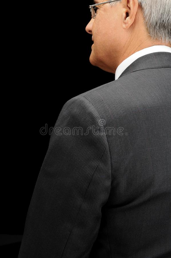 Primo piano di un uomo d'affari maturo visto da dietro dentro il profilo sopra un fondo nero immagine stock libera da diritti