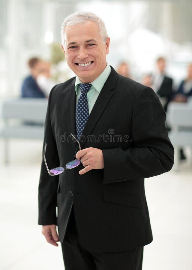 Primo piano di un uomo d'affari senior serio con i vetri a disposizione fotografie stock