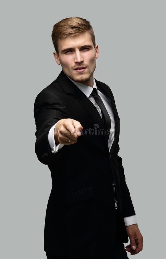 Primo piano di un uomo d'affari sicuro che indica il suo dito in avanti immagine stock