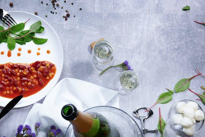 Primo piano di una bottiglia di champagne, piatto bianco con i fagioli inscatolati, aglio, mandorla, pomodori su un fondo leggero fotografia stock