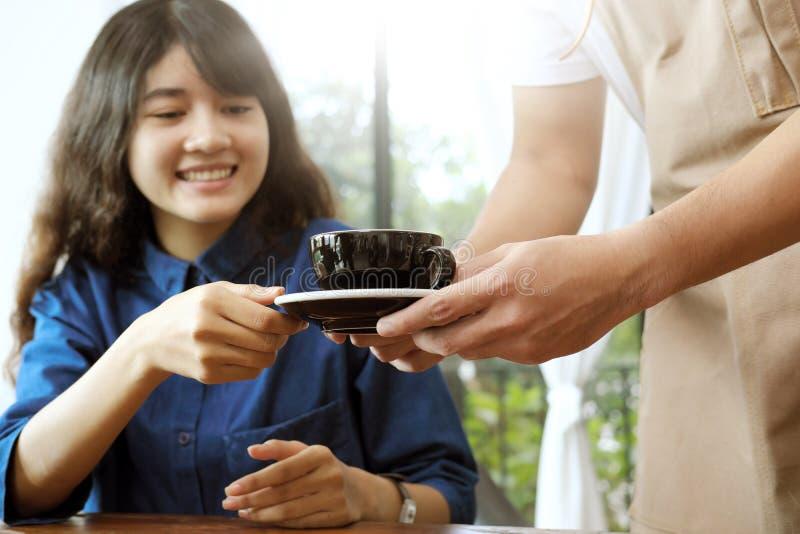 Primo piano di una cameriera di bar che serve una tazza di caffè al giovane beautifu fotografia stock
