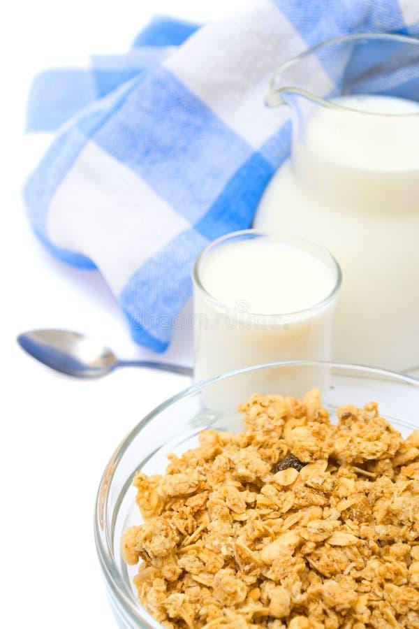Primo piano di una ciotola di cereale con una brocca di latte fresco, isolata immagine stock libera da diritti