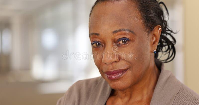 Primo piano di una donna afroamericana anziana sorridente sul lavoro immagini stock libere da diritti