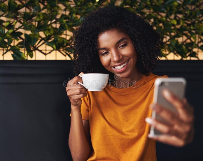 Primo piano di una donna in caffè che prende selfie sullo smartphone fotografia stock