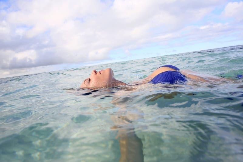 Primo piano di una donna che bagna e che galleggia nel mare immagini stock