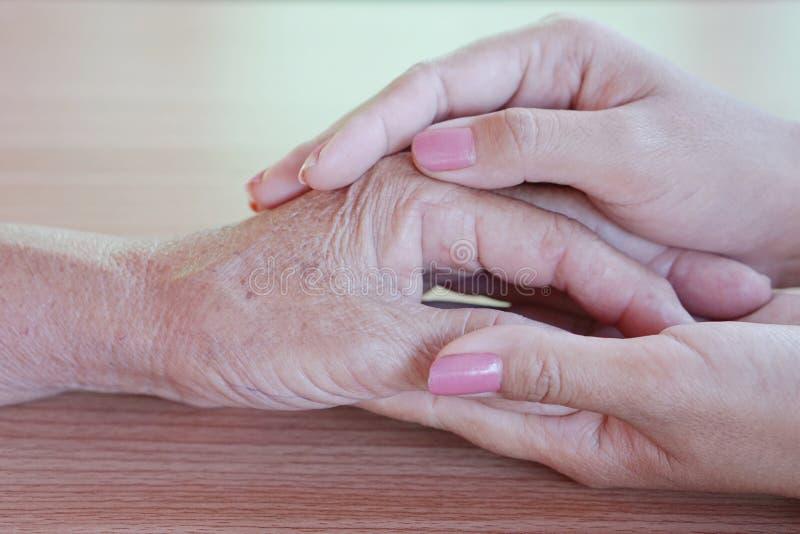 Primo piano di una donna che tiene una mano anziana del ` s della donna immagine stock libera da diritti