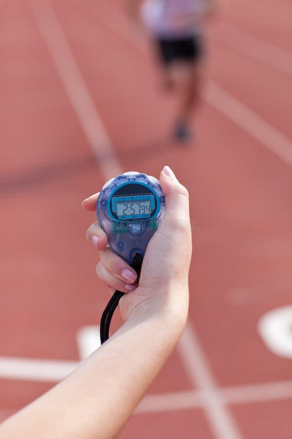 Primo piano di una donna che tiene un cronometro fotografia stock libera da diritti