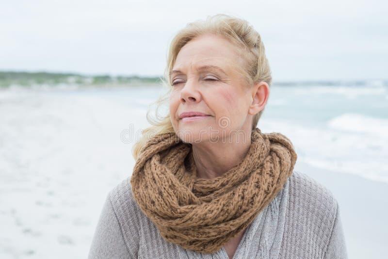 Primo piano di una donna senior contemplativa alla spiaggia immagini stock libere da diritti