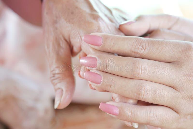 Primo piano di una figlia che tiene la sua mano del ` s della madre il giorno del ` s della madre immagine stock
