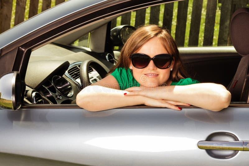Primo piano di una giovane donna graziosa in sua nuova automobile fotografia stock