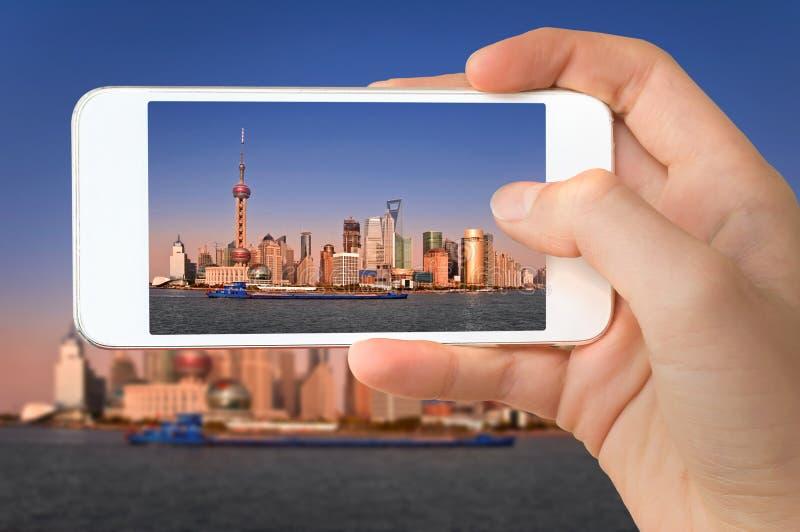Primo piano di una mano con lo smartphone che prende un'immagine dell'orizzonte di Shanghai e del fiume Huangpu Cina fotografia stock libera da diritti