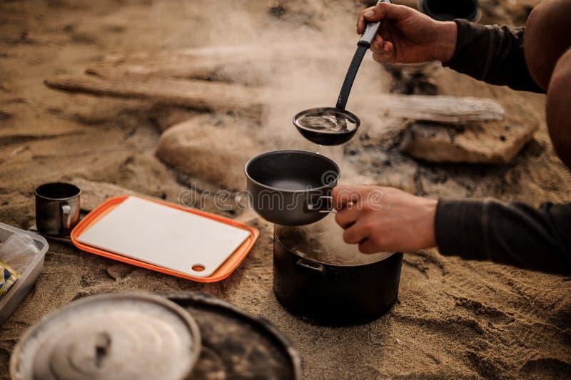 Primo piano di una minestra di versamento dell'uomo con una siviera fotografia stock