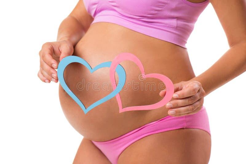 Primo piano di una pancia incinta con i cuori rosa e blu fotografia stock libera da diritti