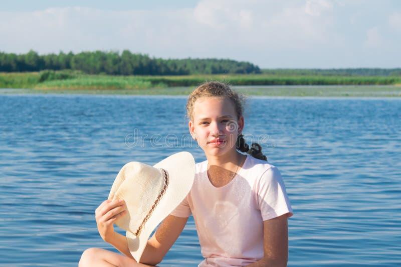 Primo piano di una ragazza che tiene un cappello in sua mano contro il contesto di bello paesaggio fotografia stock