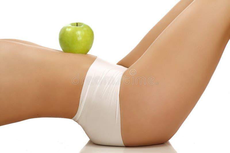 Primo piano di una ragazza perfetta che mostra una frutta sul suo corpo fotografia stock libera da diritti