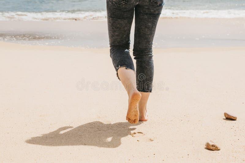 Primo piano di una ragazza scalza che cammina lungo la spiaggia immagini stock libere da diritti