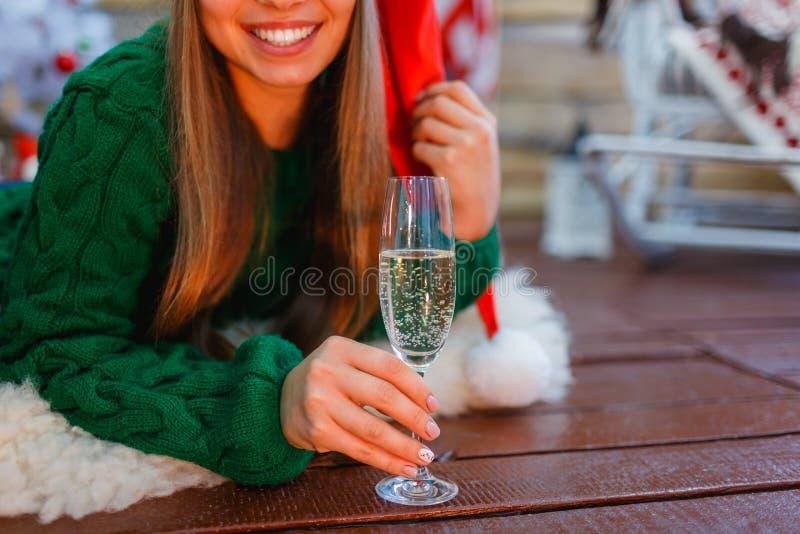 Primo piano di una ragazza in un cappello di Santa, il suo sorriso, con un vetro di champagne in sue mani immagine stock