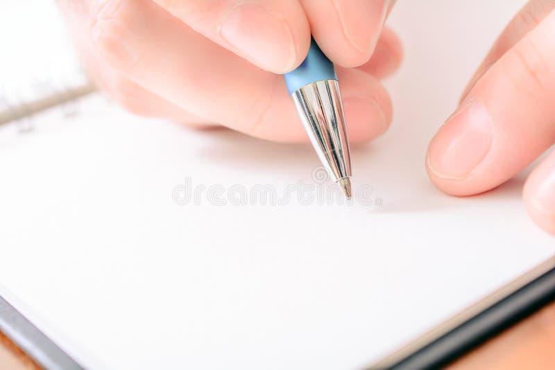Primo piano di una scrittura maschio della mano in un organizzatore in bianco With un biro immagini stock