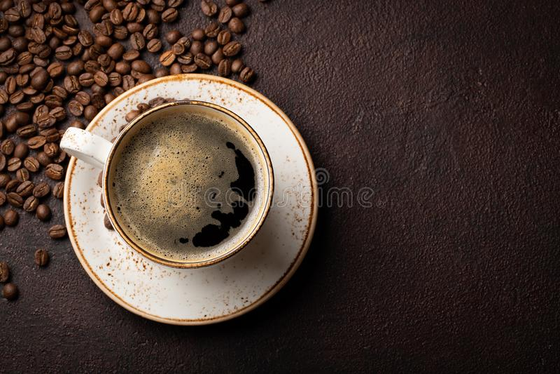 Primo piano di una tazza di caffè nero e dei chicchi di caffè su un fondo scuro Vista superiore con lo spazio della copia Disposi fotografia stock libera da diritti