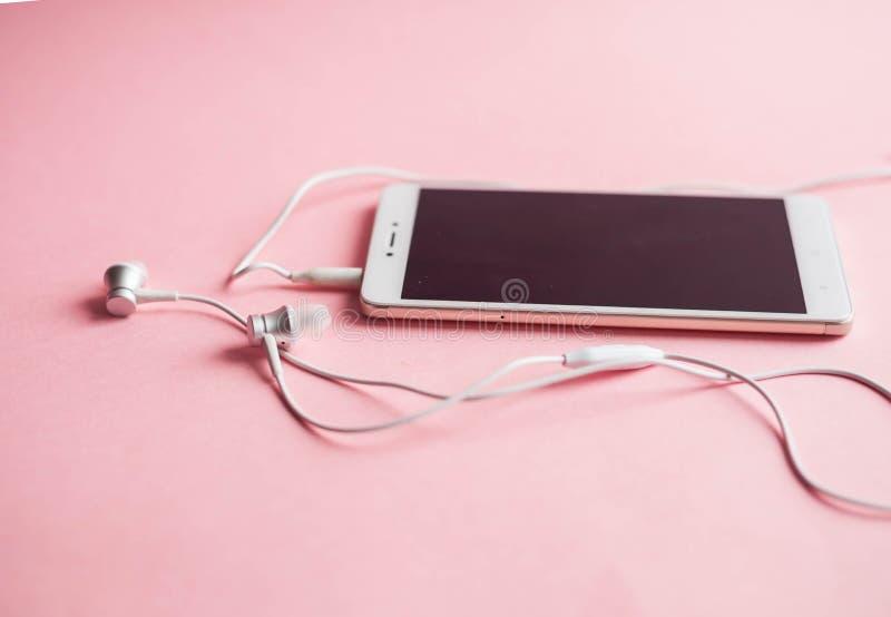 Primo piano di uno smartphone con le cuffie su un fondo rosa Vista da sopra Ascolti musica fotografia stock libera da diritti