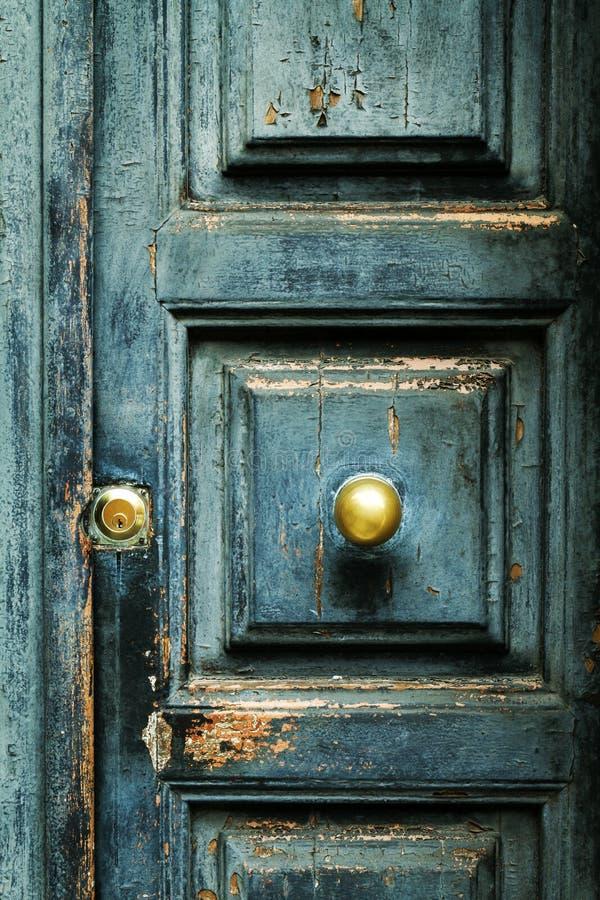 Primo piano di vecchia porta antica strutturata del turchese blu con il Br dell'oro immagini stock libere da diritti