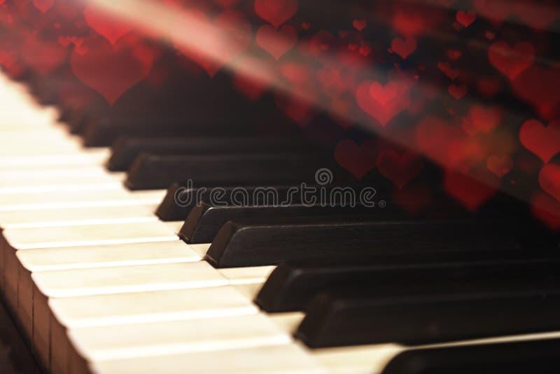 Primo piano di vecchia tastiera di piano, fuoco selettivo, tonalità morbida Fondo di San Valentino, piano d'annata e cuori del bo fotografia stock
