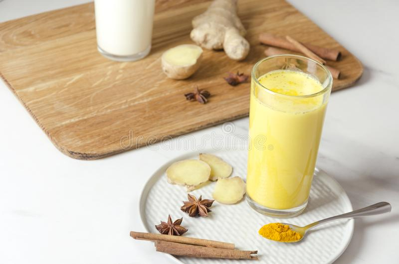 Primo piano di vetro di latte dorato con gli spieces Latte caldo della curcuma con le erbe Bevanda sana del vegano immagini stock libere da diritti