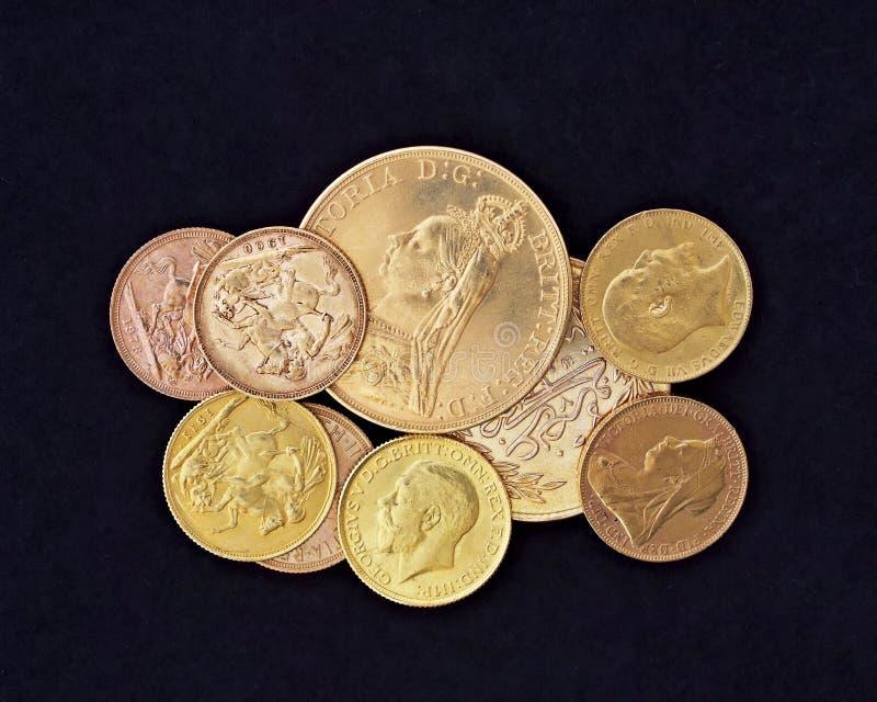 Primo piano dorato delle monete sul fondo nero del velluto immagini stock