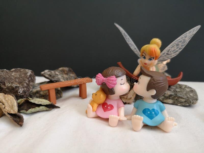 Primo piano e macro colpo dei bambini bacianti miniatura nel giardino mentre fatato Tinkerbell che insegue dietro immagini stock libere da diritti
