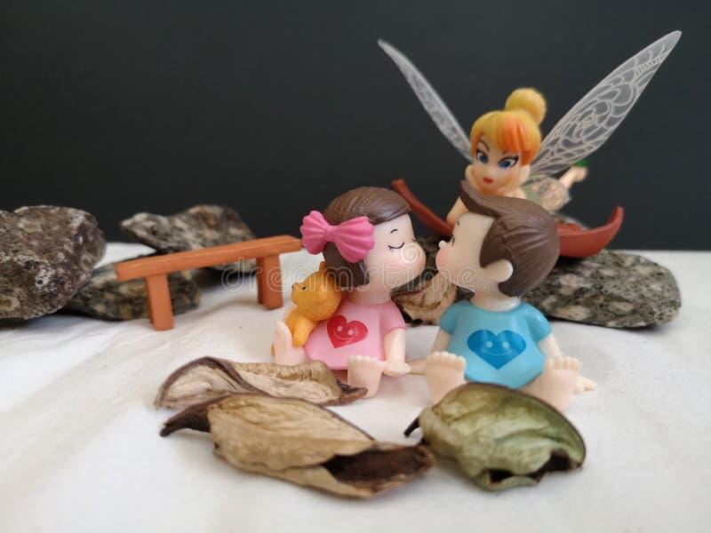 Primo piano e macro colpo dei bambini bacianti miniatura nel giardino mentre fatato Tinkerbell che insegue dietro fotografie stock libere da diritti