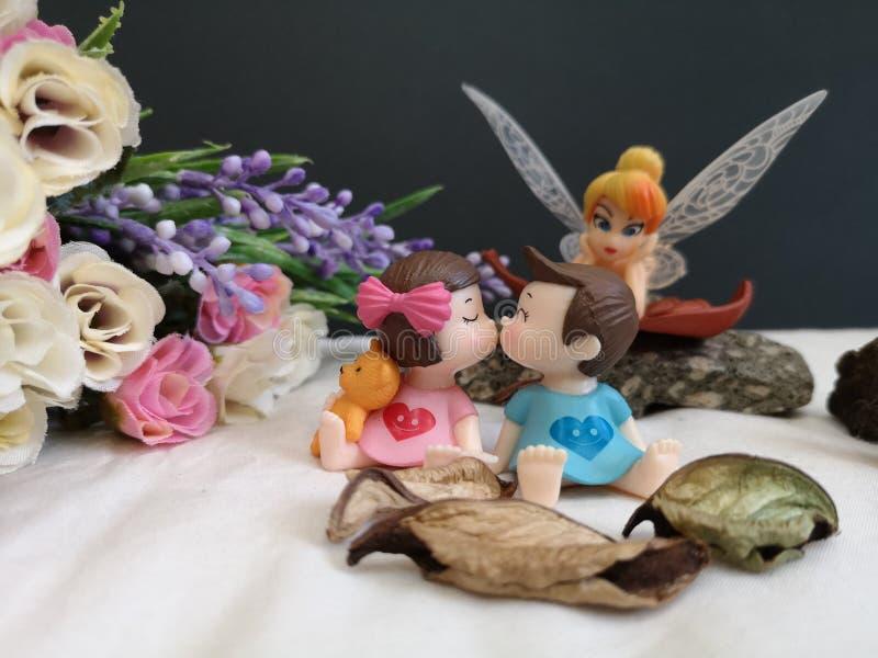 Primo piano e macro colpo dei bambini bacianti miniatura nel giardino mentre fatato Tinkerbell che insegue dietro fotografia stock libera da diritti