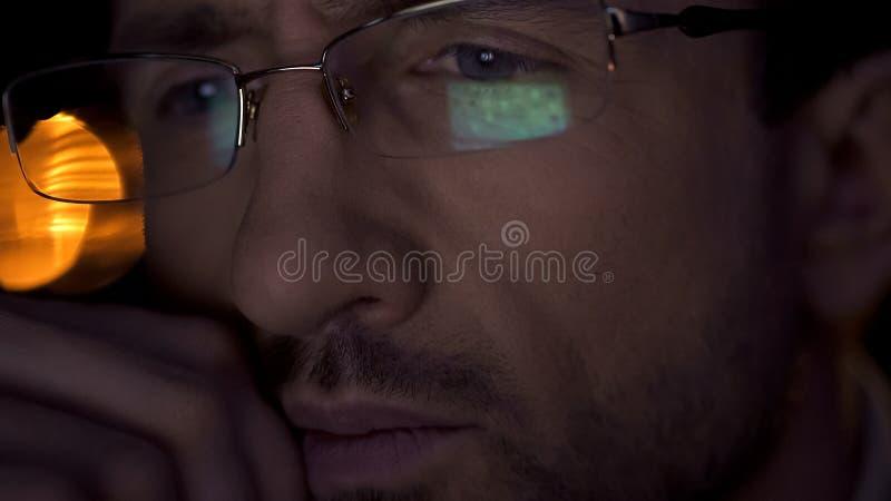 Primo piano eccellente del fronte dell'uomo d'affari, maschio in occhiali che esaminano lo schermo del PC fotografia stock libera da diritti