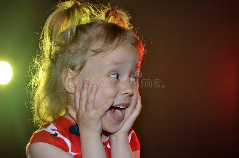Primo piano emozionale della bambina su un fondo nero con luminoso fotografie stock