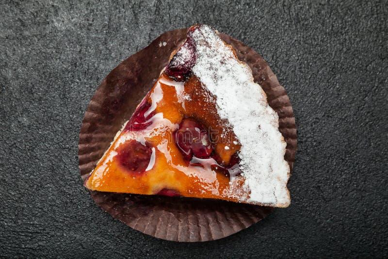 Primo piano, fetta una torta festiva della frutta su una tavola nera immagine stock libera da diritti