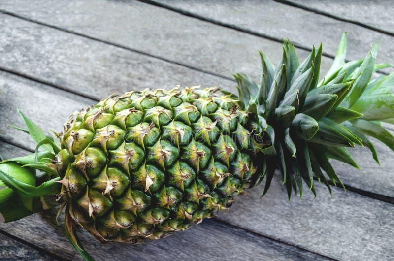 Primo piano fresco verde della frutta dell'ananas su un vecchio fondo di legno con la luce della natura immagini stock libere da diritti