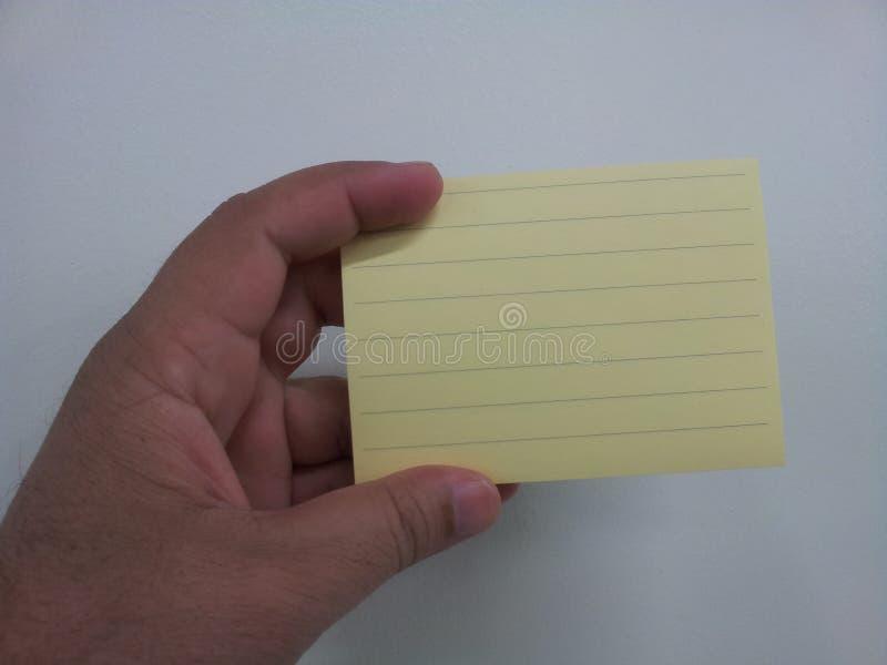 Primo piano, fuoco selettivo: Mano che tiene carta per appunti appiccicosa gialla immagini stock libere da diritti