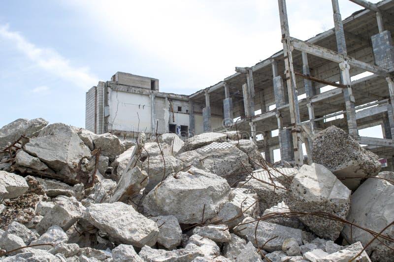 Primo piano grigio concreto dei detriti sui precedenti del resti della costruzione distrutta contro il cielo Fondo fotografia stock libera da diritti