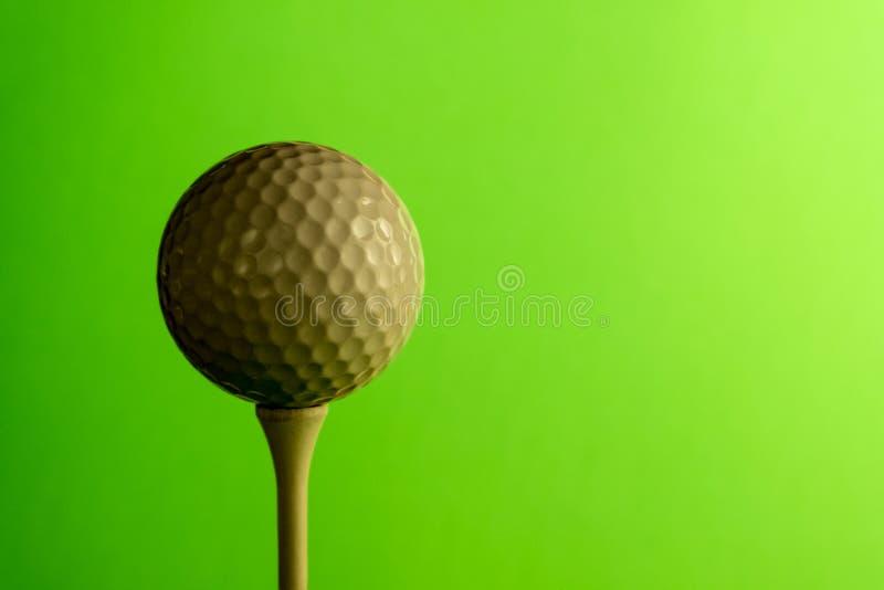Primo piano il lato ombreggiato di una palla da golf su un T Copi lo spazio Fondo verde intenso dell'insalata fotografia stock