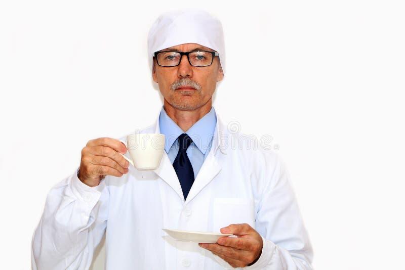 Primo piano - il medico tiene in sua mano una tazza di caffè fotografia stock libera da diritti